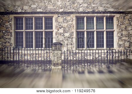 Blurry edged view of eight old glass paned windows with stone walls and iron fence in front