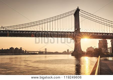 Tranquil sunset behind Brooklyn Bridge with a sunburst below the span silhouetting the tower and suspension cables above the water of the East River