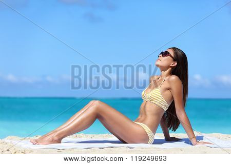 Beach sunglasses woman sun tanning in sexy bikini. Full body girl lying down getting a suntan on skin wearing eyewear. Skincare solar uv rays protection concept.