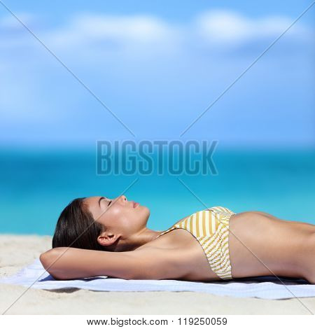 Suntan woman relaxing on summer beach vacation. Sexy young ethnic adult in yellow stripes bikini sleeping lying down on white sand dreaming with sky copyspace for tropical travel destination concepts.