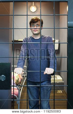The man in glasses standing near lattice in a prison cell