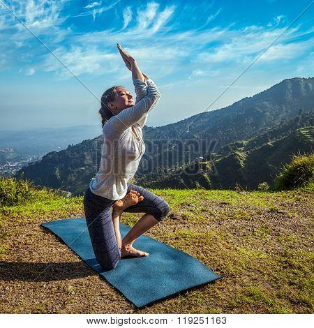 Young woman doing Ashtanga Vinyasa yoga advanced difficult asana Vatayanasana (Horse pose) outdoors in Himalayas mountains. Himachal Pradesh, India