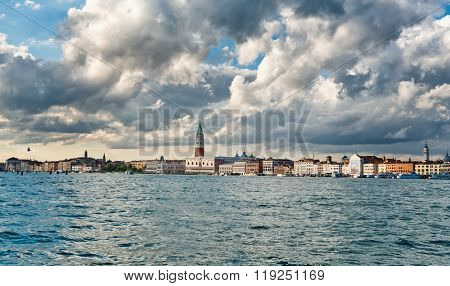 Venice cityscape looking across the water of the Giudecca Canal towards the Campanile, Doges palace and waterfront of Cannaregio, dramatic cloudy sky