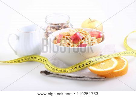 Corn And Rice Flakes With A Fresh Apple, An Orange And A Measuring Tape On A White Background