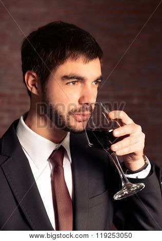 Man sniffing red wine in glass on brick wall background