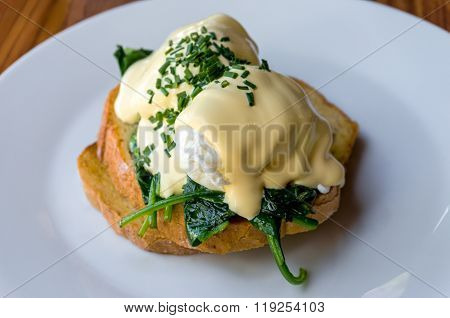 Eggs Benedict with spinach on toast. Poached egg on toast with spinach and chives on white plate. Healthy breakfast. Selective focus shallow dof