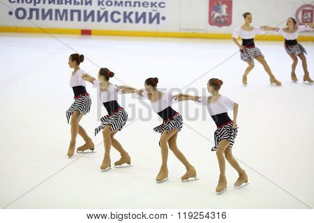 MOSCOW - APR 26, 2015: The team of girls in striped skirts performs on the skate at the Cup in synchronized figure skating in the sports complex Olympiysky