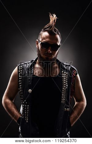 Vertical shot of a young male punk with a Mohawk hairstyle on dark background