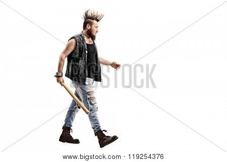 Full length profile shot of an angry punk rocker walking with a baseball bat in his hand isolated on white background
