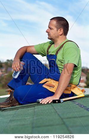 Worker Installing Bitumen Shingles - Taking A Break
