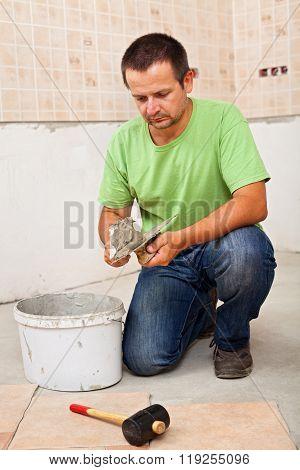 Man Installs Ceramic Floor Tiles - Preparing The Adhesive