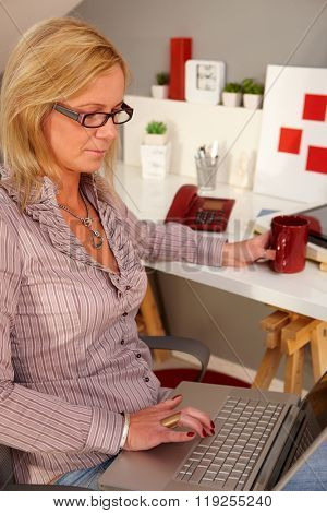 Blonde woman holding laptop computer on lap, working at home.