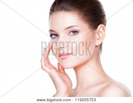 Portrait of woman with healthy face applying cosmetic cream under the eyes.