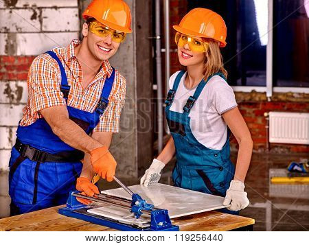 Happy young couple professional builder cutting ceramic tile.