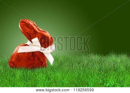 Wrapped Easter bunny with red aluminium on grass on grass on green background