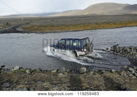 ASKJA ICELAND - 29 AUGUST 2012: Big blue four by four off road car crossing a river stream on the rouad to Askja in the Icelandic Tundra