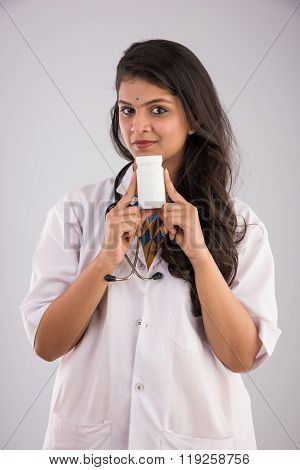 Portrait of Indian female doctor holding white pill bottle, asian doctor showing white pill bottle,