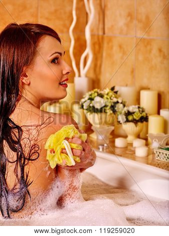 Young woman keeps sponge take bubble  bath. Woman washing her shoulder.