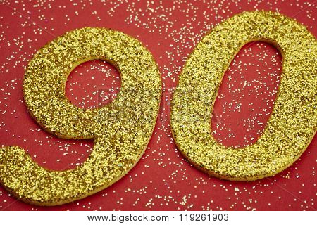 Number Ninety Golden Color Over A Red Background. Anniversary.
