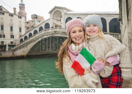 Mother And Daughter With Italian Flag In Front Of Rialto Bridge