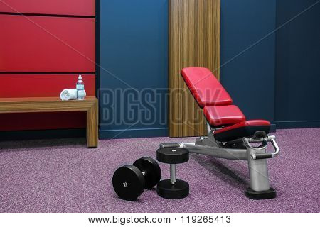 Exercises bench and dumbbells in fitness room