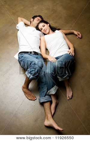 Sexy young ethnic couple in casual outfits relaxing