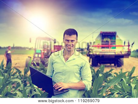 Farmer With Laptop During Harvest