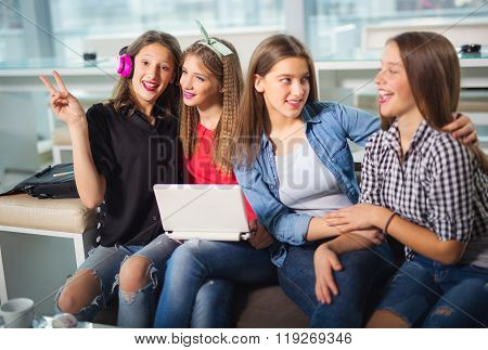 Portrait of four young women sitting at the table in the cafe, selective focus