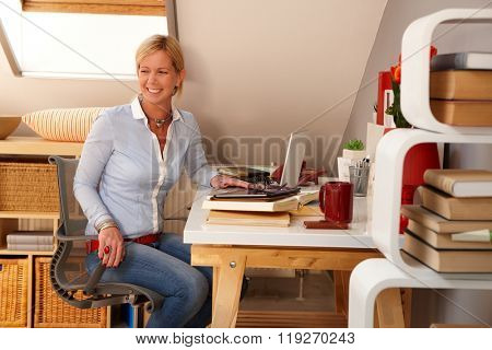 Happy blonde woman sitting at desk, working at home, looking away.