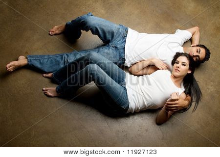 Sexy young multiracial couple in blue jeans relaxing on the floor