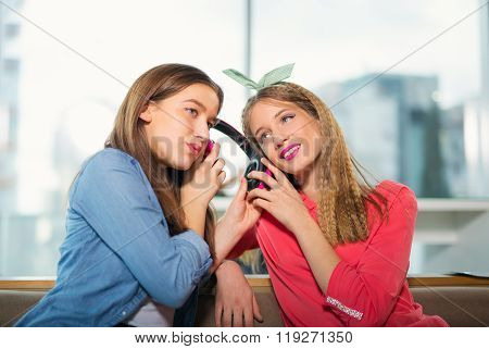 Female friends listening to music together, selective focus