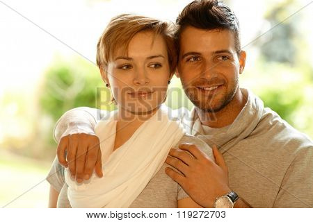 Closeup portrait of young loving couple embracing, looking away.