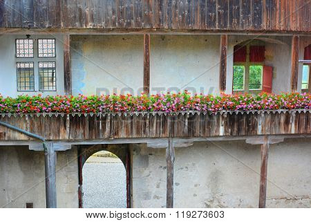 GRUYERES, SWITZERLAND - JULY 8, 2014: Gruyeres Castle Detail. Flowers wrap around the castle wall walkway.