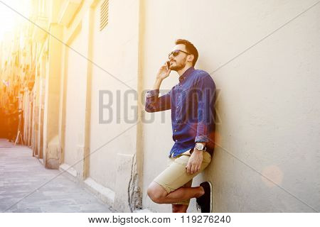 Confident man having mobile phone conversation while waiting for someone outdoors