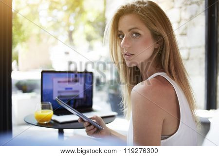 Pretty hipster girl posing with smart phone in hand while sitting in cafe with laptop computer