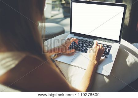 Hipster girl keyboarding on net-book while relaxing at home