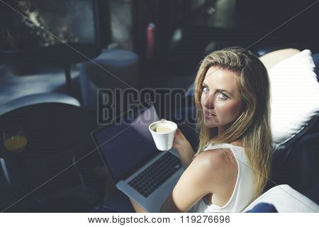 Woman with mug of cappuccino and laptop computer on knees posing for camera