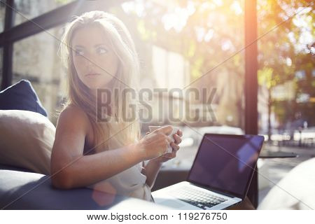 Beautiful female enjoying hot beverage while resting after work on portable laptop computer