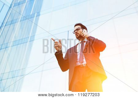 Smart man employer showing finger on something while talking on cell telephone outside