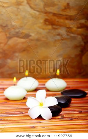 Hot spa stones, lit candles and tropical frangipani flower on bamboo mat