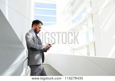 Male office worker using his portable digital tablet while waiting start conference