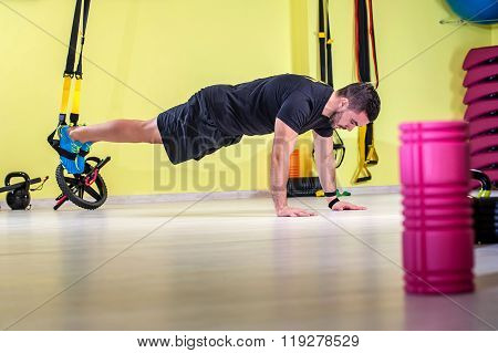 Man does push ups with fitness straps