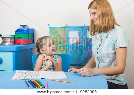 The Girl Is Happy And Looks At The Teacher In Kindergarten