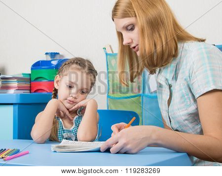 Five-year Girl With Interest Looking Notebook And Listening To The Explanation Of The Teacher