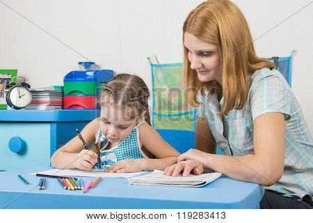 The Girl Draws In A Notebook With A Ruler, The Teacher Helps Her