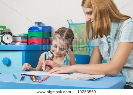A Teacher Helps A Five-year Girl With A Ruler To Draw