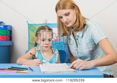 Mentor Shows Five Children To Write Letters Correctly
