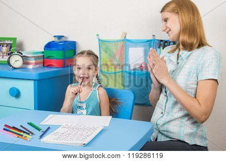 Five-year Girl And A Tutor Is Fun Sitting At The Table And Enjoy