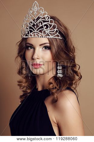 beautiful young woman with dark curly hair and evening makeup, with precious crown on head