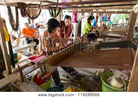 Woman Using Traditional Loom To Weave Thailand Textile